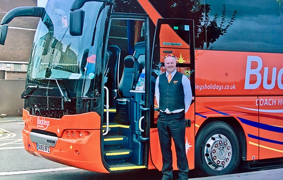 driver stood in front of a buckleys private hire coach