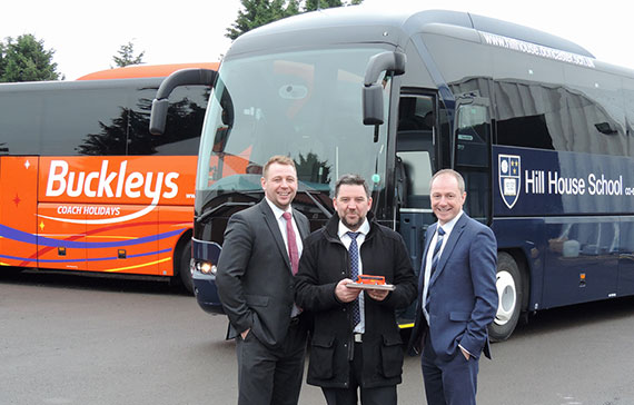three men stood in front of a buckleys private hire coach