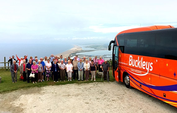 social club stood in front of a buckleys private hire coach